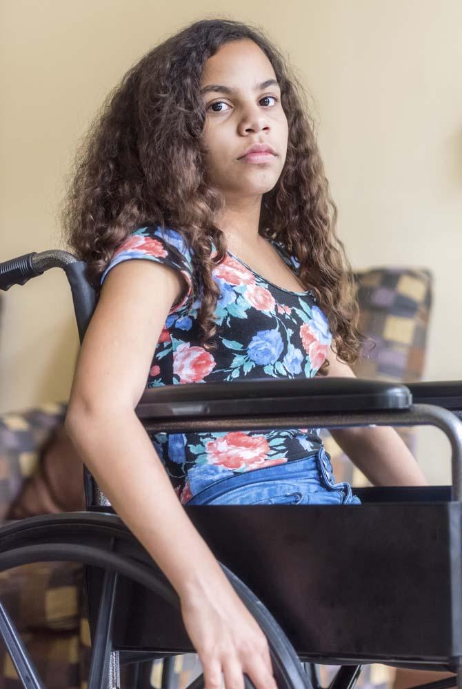 Latino teenage girl in wheel chair looking at the camera
