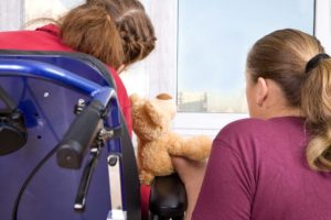 Back of girl in wheelchair holding a stuffed bear and sitting with woman
