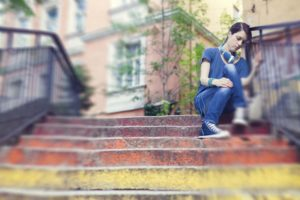 Unhappy teenage girl sitting outside on steps