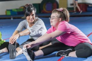 A fitness instructor in a gym working with a teenage girl with down syndrome. They are sitting on the floor, stretching.