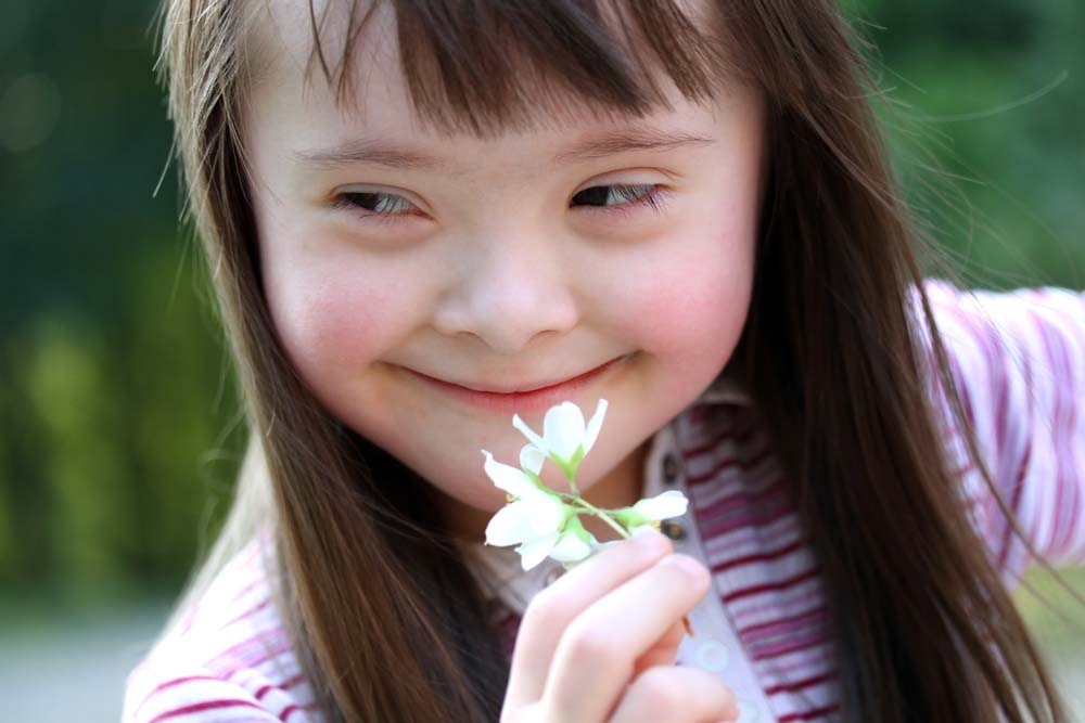 Young white girl with down syndrome girl holding a flower and smiling.
