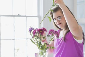A teenage girl with down syndrome puts pink and purple flowers in a vase.
