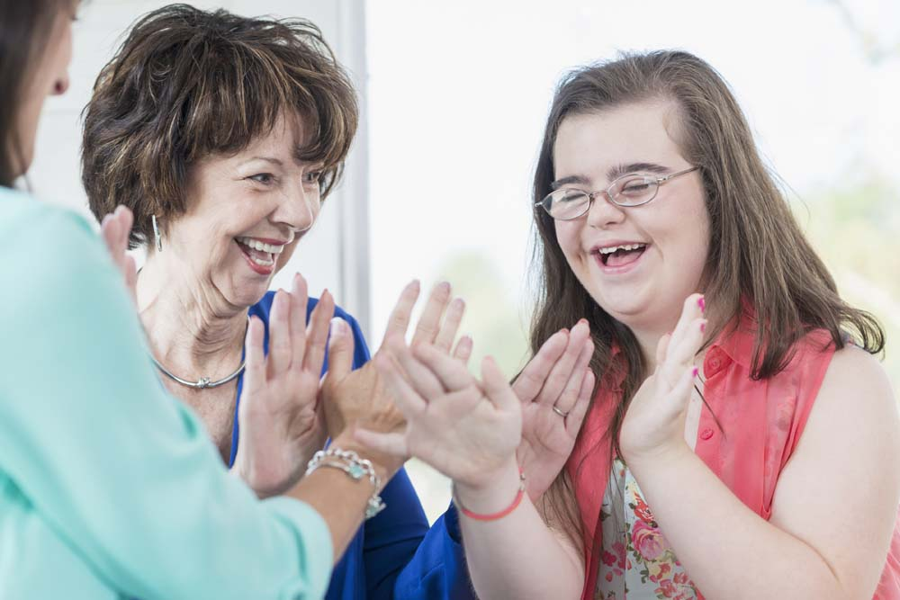 A happy teenage girl with down syndrome playing patty cake with her grandmother and mother.