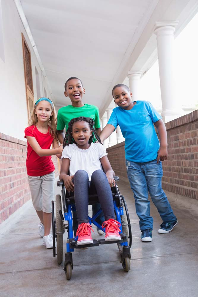 three kids standing behind a girl in a wheelchair