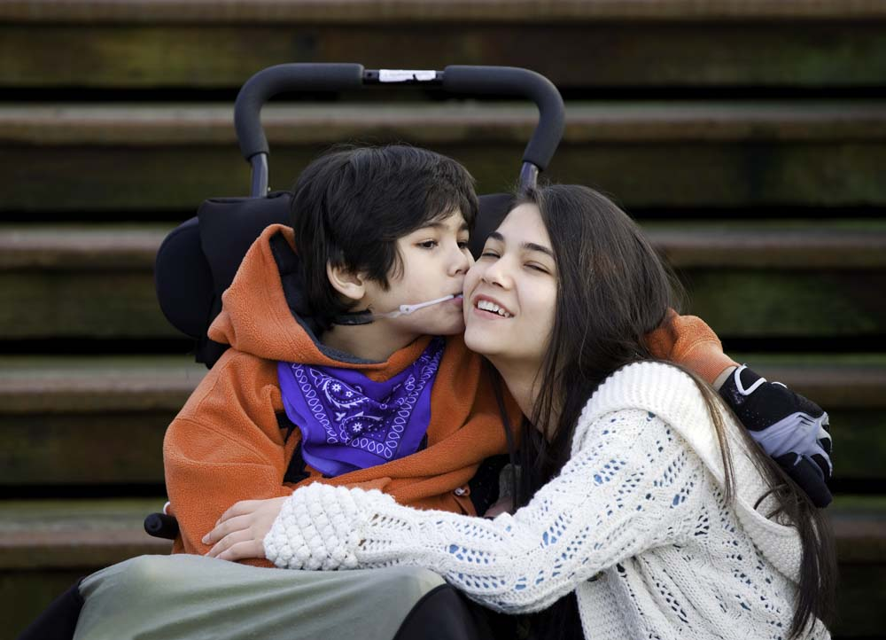 young boy in a wheelchair kissing older girl on the cheek with stairs in the background