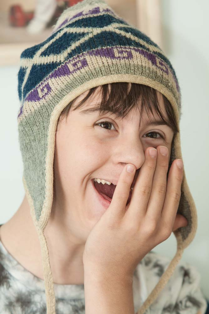 young boy with knit hat laughing and covering his face with his hand