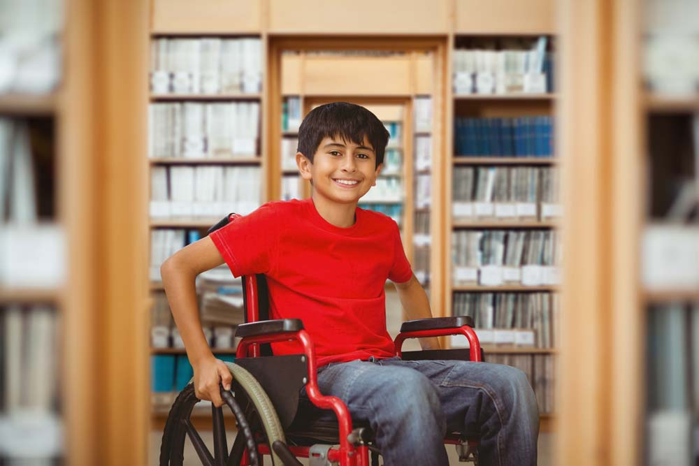 young smiling Latino boy in a wheelchair in a libary