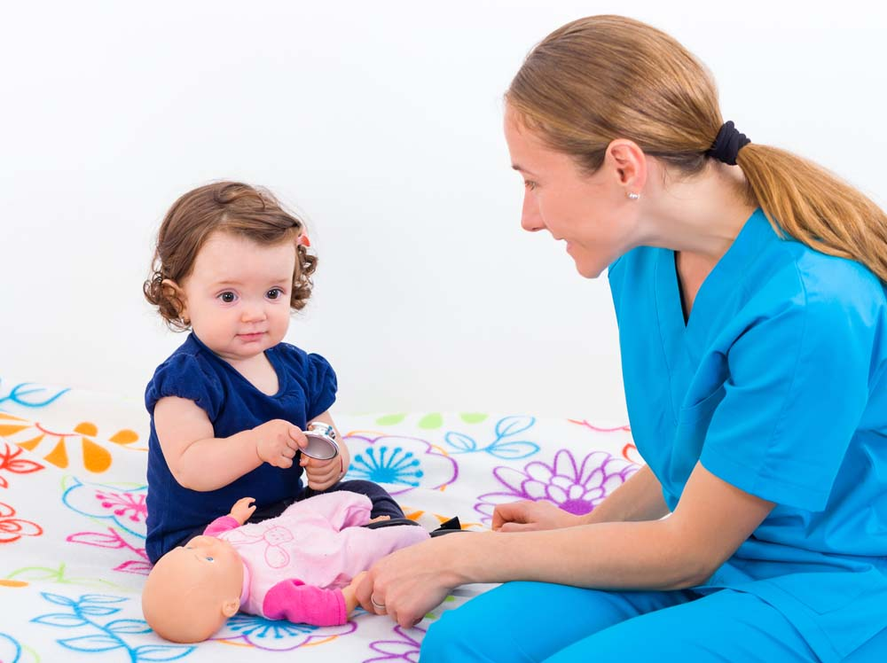 young female nurse with baby girl showing her how to use a stethoscope