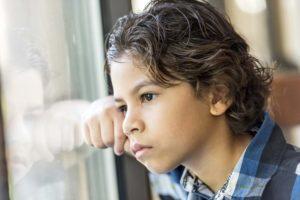Pensive Latino little boy looking through a window