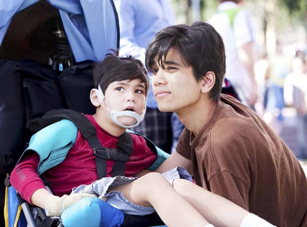 Boy in wheelchair with an older boy sitting next to him