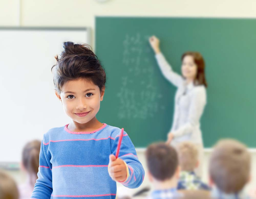 young student holding a pen with teacher at chalkboard in the background