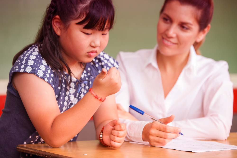 Asian girl with disability looks at her fingernails while adult sits next to her with paper and pen.