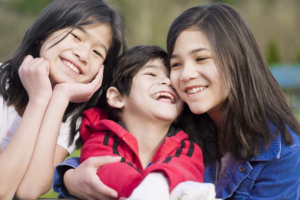 Two older Asian sisters cuddle with a younger brother with a disability.