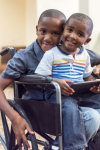 Black/African-American smiling child in a wheelchair playing with his little brother