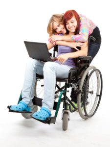 a young lady hugging another sitting in a wheelchair holding a laptop