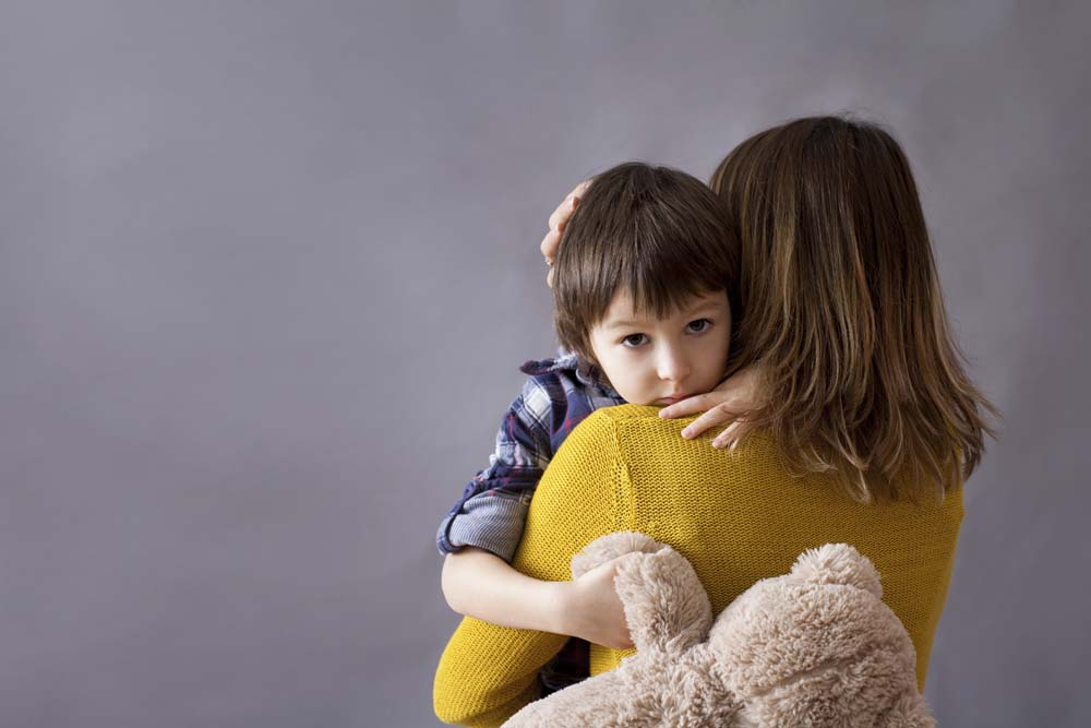 Sad little child, boy, hugging his mother, stuffed bear in his hand.