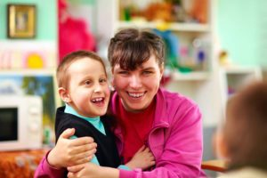 woman holding a boy who is smiling with a blurry background
