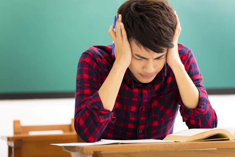 Stressed Asian student studying for exam in classroom.