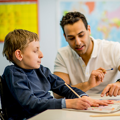 A male teacher helps a student with a disability.